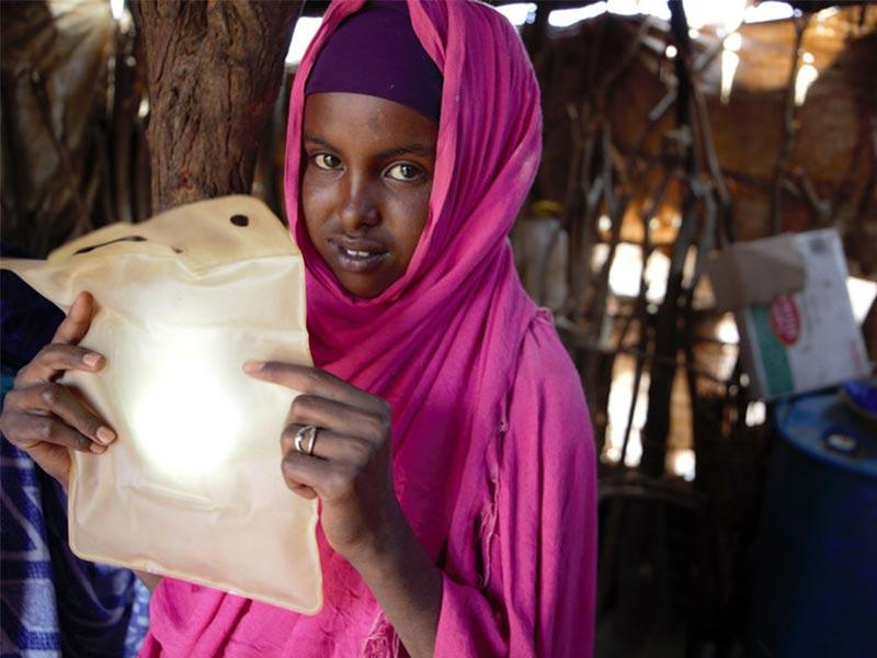 A recipient of ShelterBox aid holding her LuminAid solar light